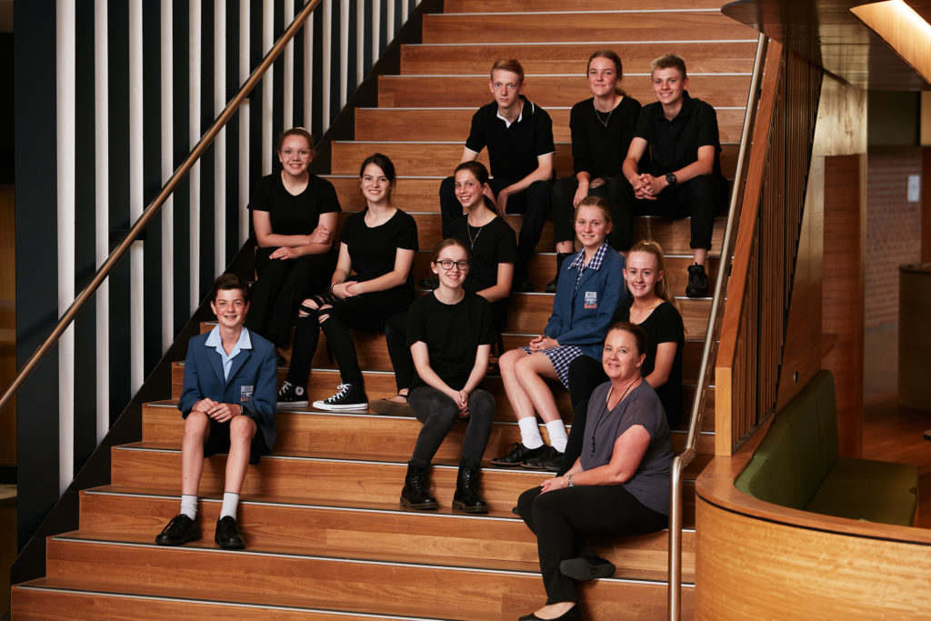 luther-college-students-wearing-black-sit-with-teacher-on-wooden-staircase